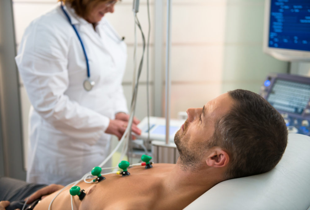Cardiology NP performs a cardiac test on a patient