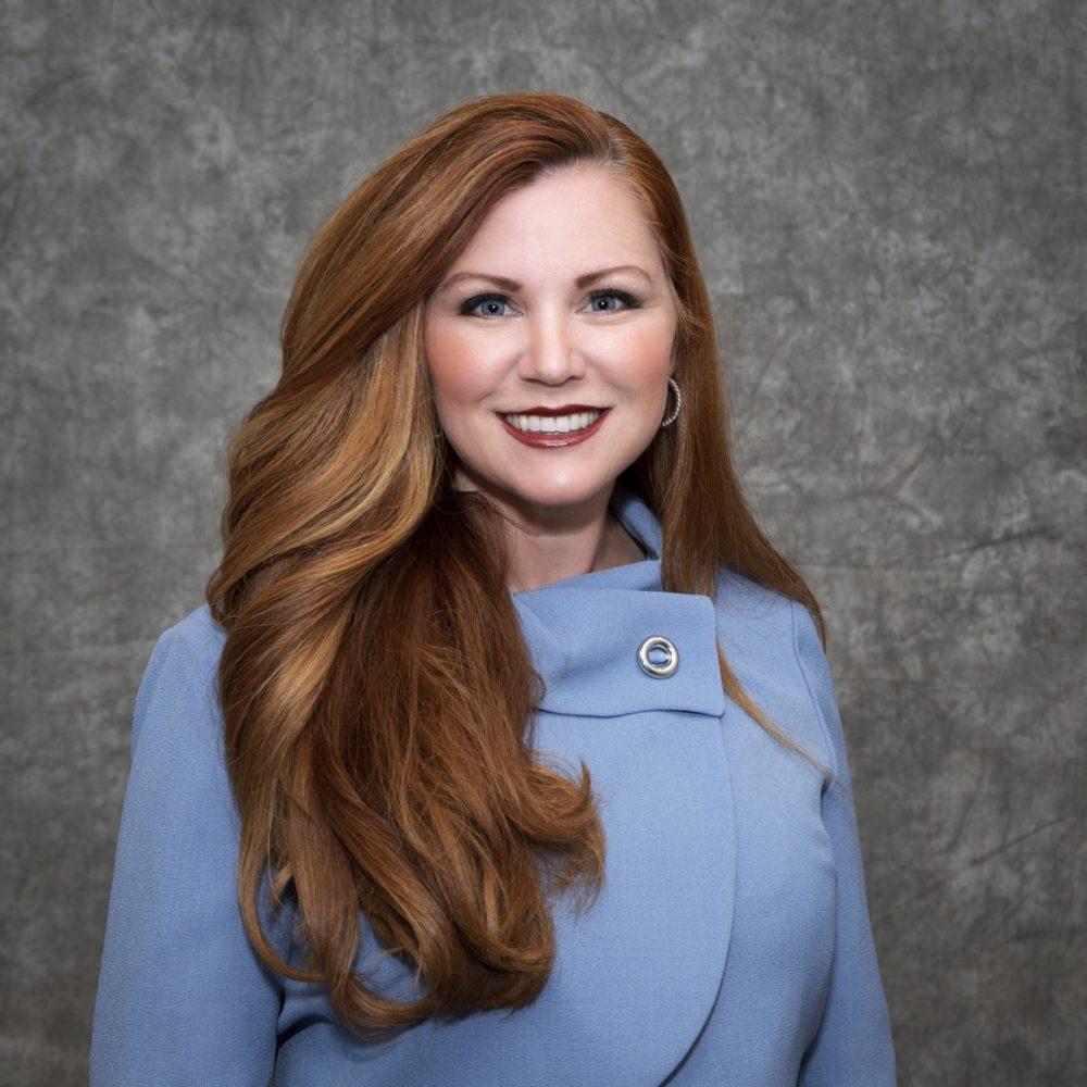 Dr. Sophia Thomas smiles wearing a blue dress coat
