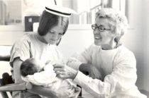 Black and white photo of a young Dr. Loretta Ford with another nurse who is holding an infant