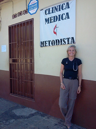 AANP member Deborah Gray stands outside a clinic during her work with Shot@Life