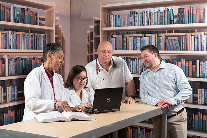 A diverse group of four NPs gather in a library around an open laptop computer and medical book