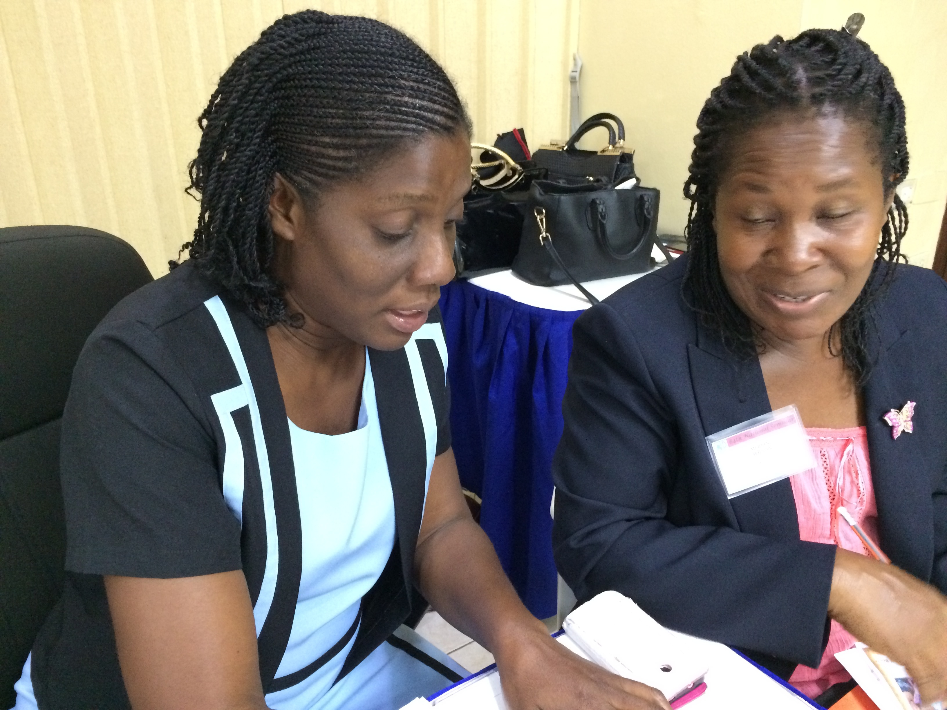 Two female nursing students review notes seated at a table