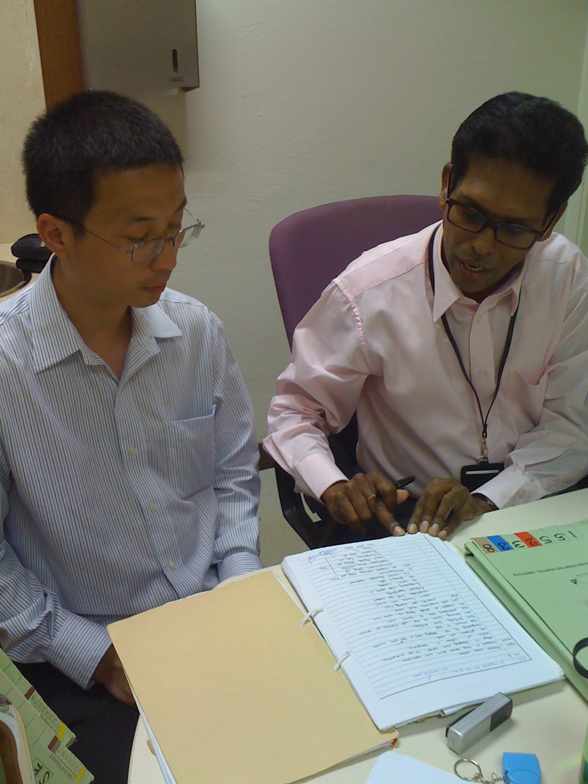 Two male nursing students review notes in a notebook at a desk