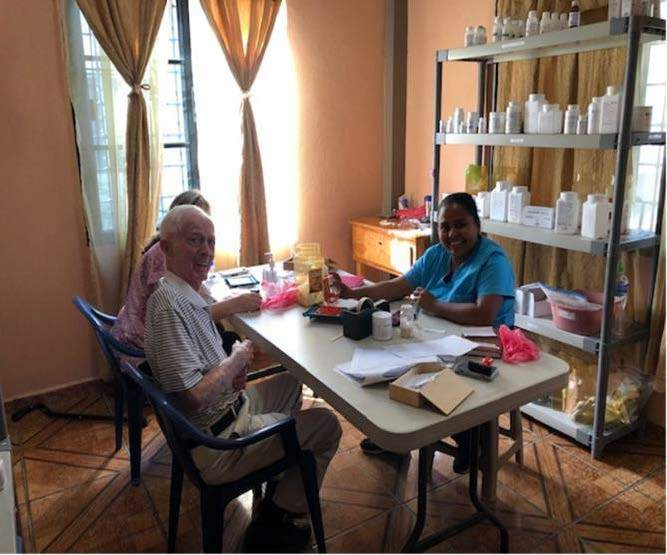 Two older patients consult a health care provider in the clinic's small pharmacy