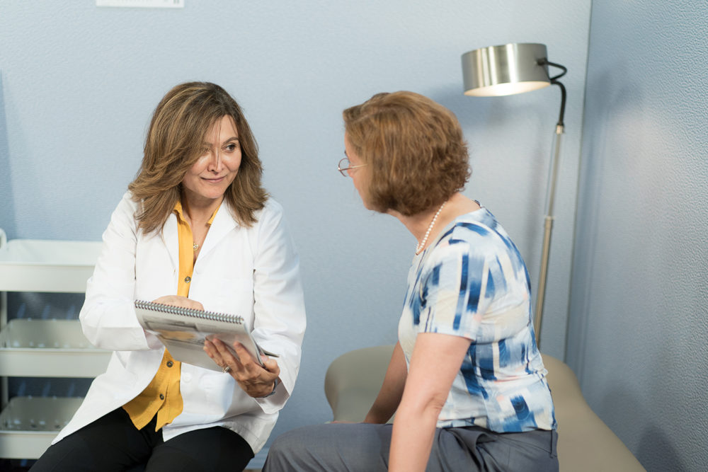 A female NP reviews a document with a female patient in an exam room