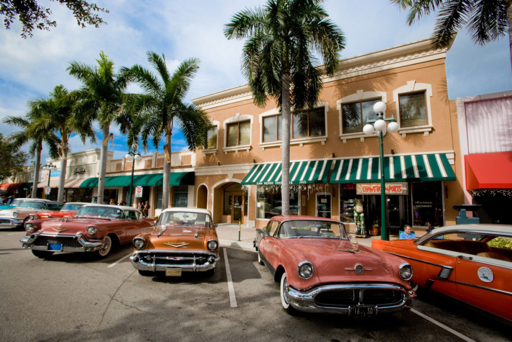 The historic downtown Hollywood, Florida, with quaint buildings and classic cars along palm tree-lined streets