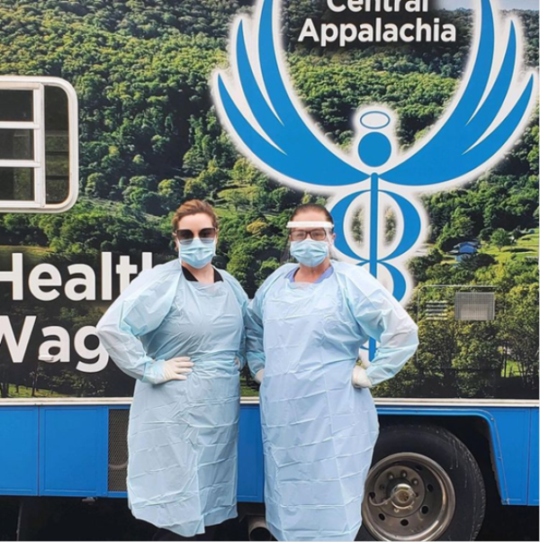 Two NPs stand with the Health Wagon, the nation's oldest mobile clinic