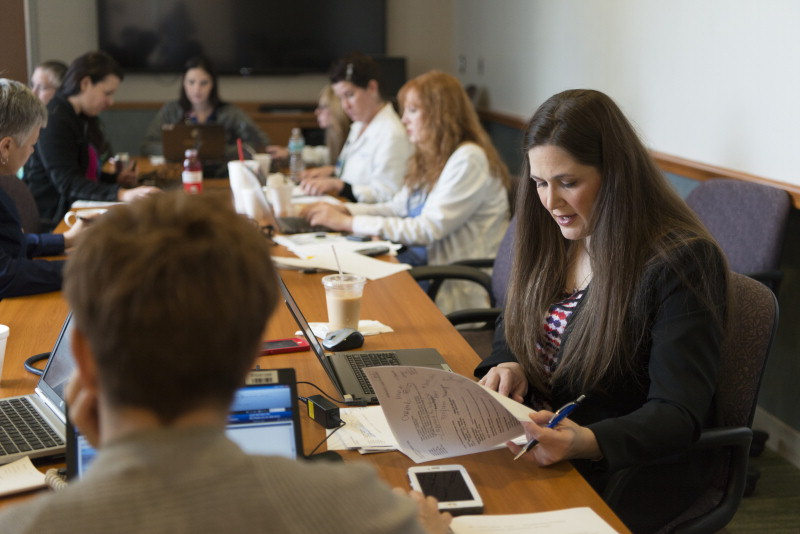 Amanda Chaney sits at a long table in a board room and speaks from her notes to a group of others seated around the table