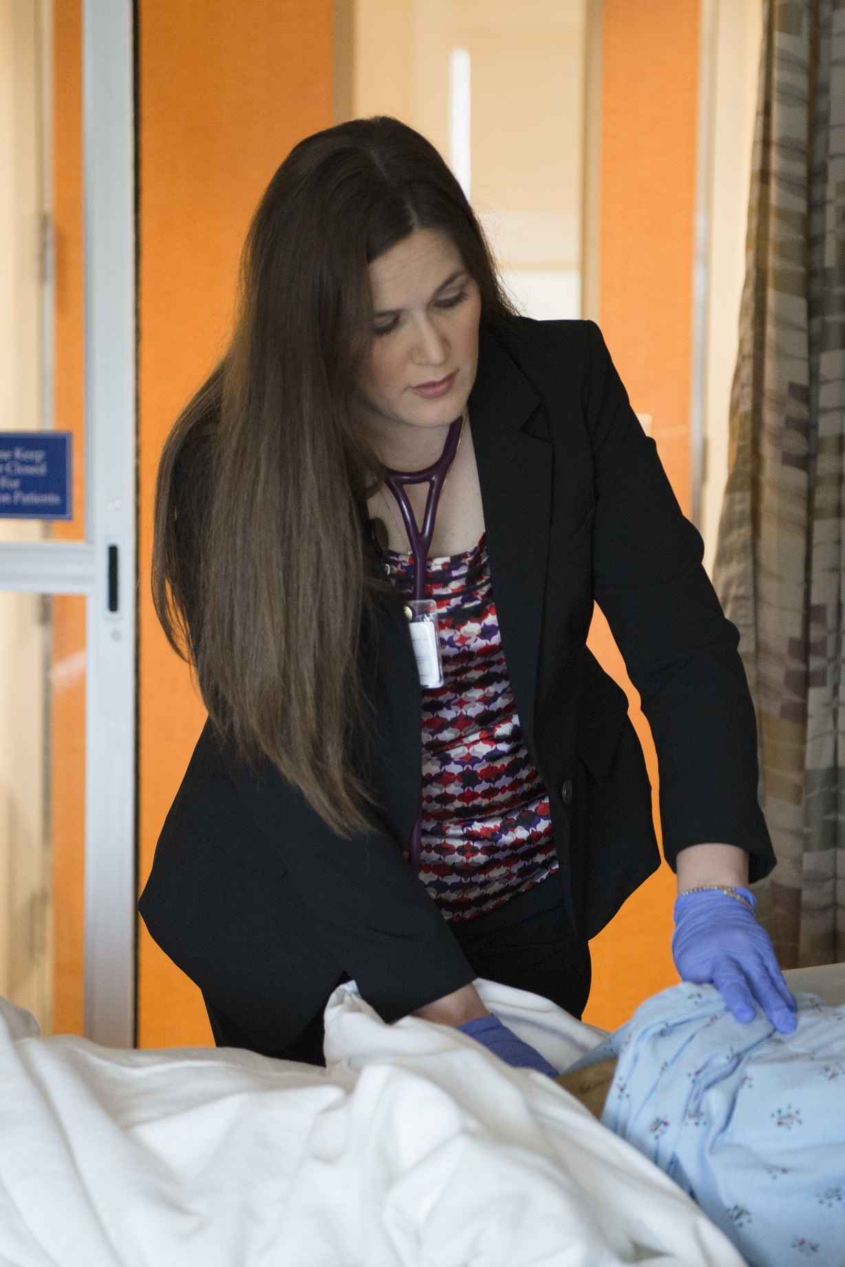 AANP Fellow Amanda Chaney wears blue gloves and examines a patient's abdominal area